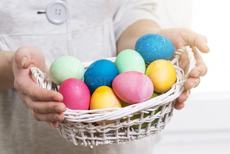 2个所有时段小鸡概念复活节彩蛋开花草被绘的被安置的年轻人 妇女为宗教复活节假日拿着篮子用五颜六色的色的鸡蛋 篮子复活节彩蛋 库存图片