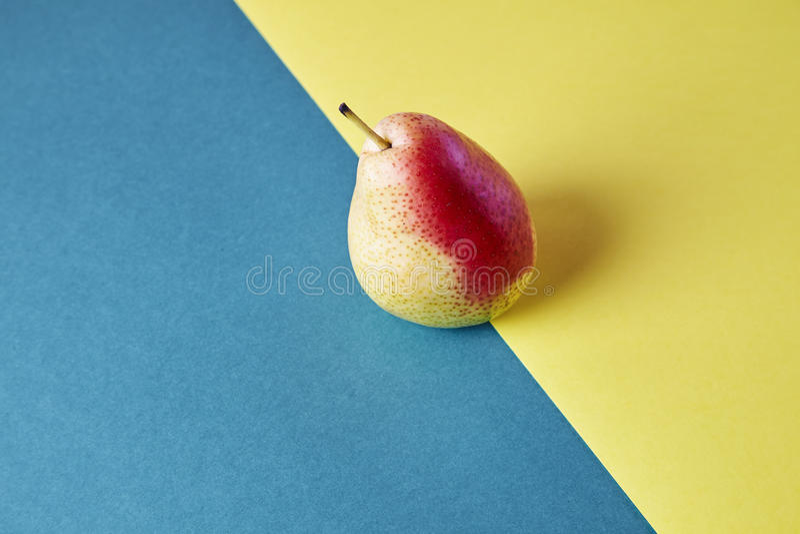 整个新鲜的成熟梨,果子视图从上面在蓝色黄色背景,现代样式食物图片,墙纸设计 免版税库存照片
