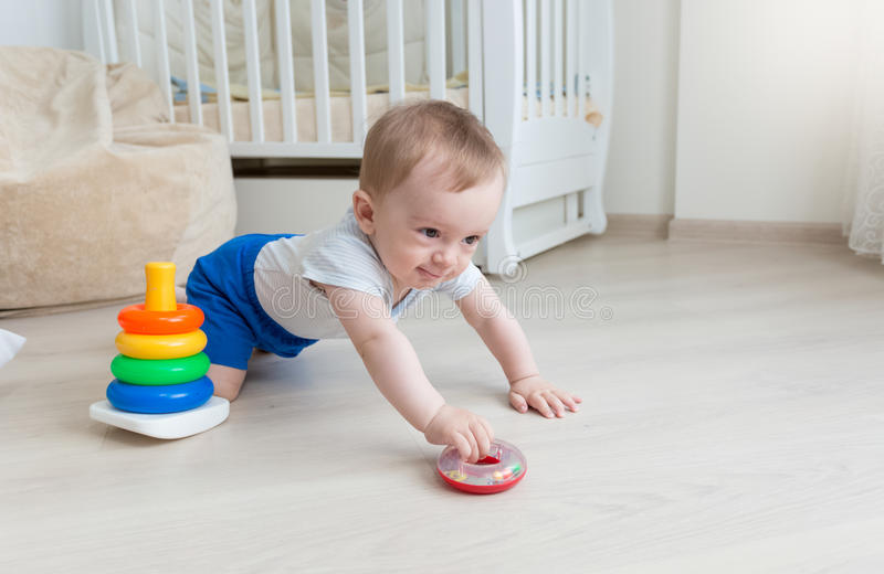 9个月使用与玩具塔的男婴在客厅 免版税库存图片