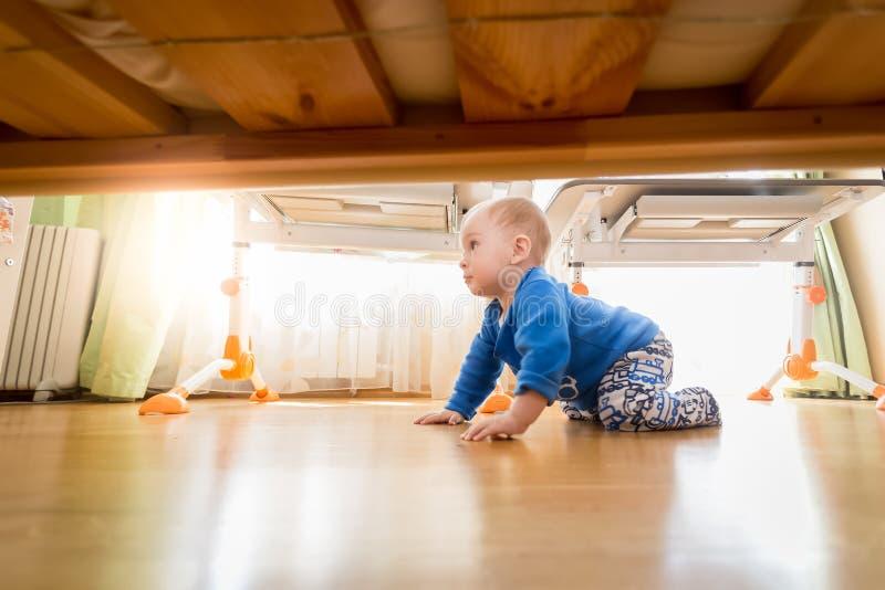 9个月爬行在木地板上的婴孩在卧室 免版税库存照片