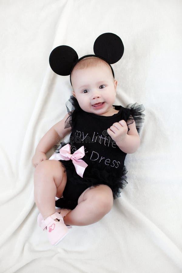 5个月的孩子获得单独乐趣,说谎在一张雪白床上 库存照片
