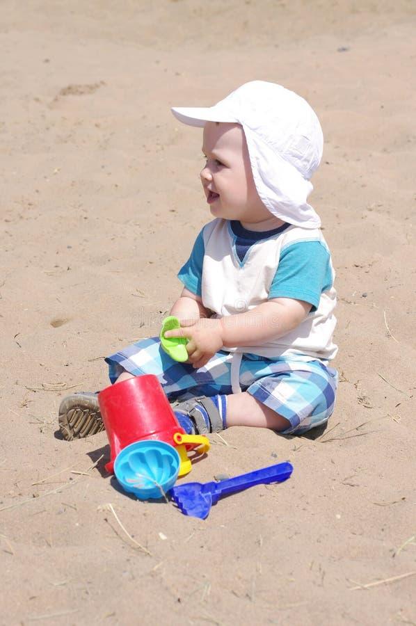 9个月的婴孩年龄使用与在海滩的沙子 免版税图库摄影