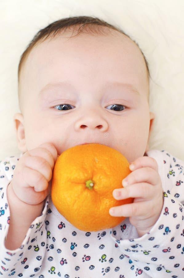 3个月的婴孩年龄用蜜桔 免版税库存图片