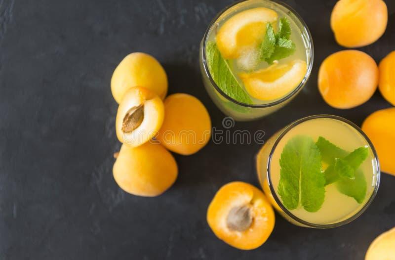 2个杯子杏子汁用薄菏,在黑暗的背景的新鲜的杏子 免版税库存图片