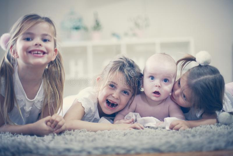 3个照相机长沙发系列女孩查找关于坐的母亲橙色纵向他们那里 有小兄弟的妹 免版税库存照片