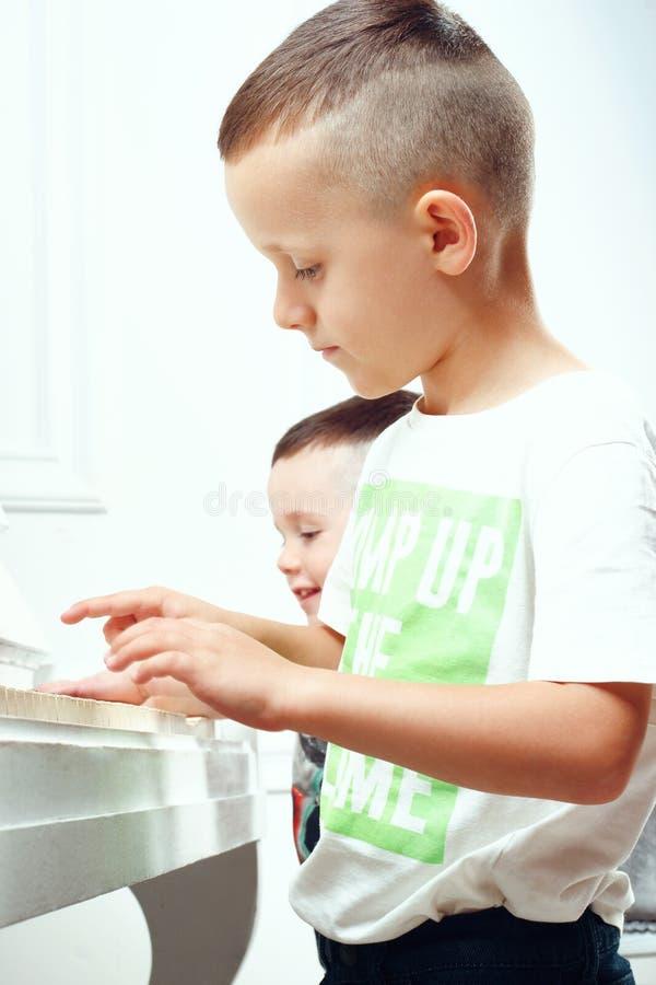 2个男孩弹钢琴 免版税库存图片