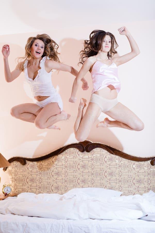 2个美丽的滑稽的女朋友,可爱的2名性感的妇女有乐趣令人惊讶的跳跃高在他们的在床上的睡衣 免版税库存照片