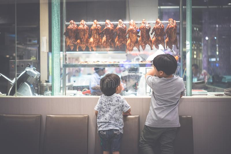 2个饥饿的兄弟观看一位厨师准备烤鸭子 免版税库存照片