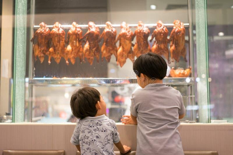 2个饥饿的兄弟观看一位厨师准备烤鸭子 库存图片
