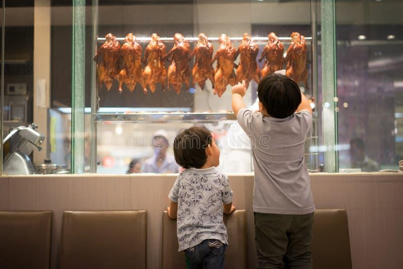 2个饥饿的兄弟观看一位厨师准备烤鸭子 库存照片