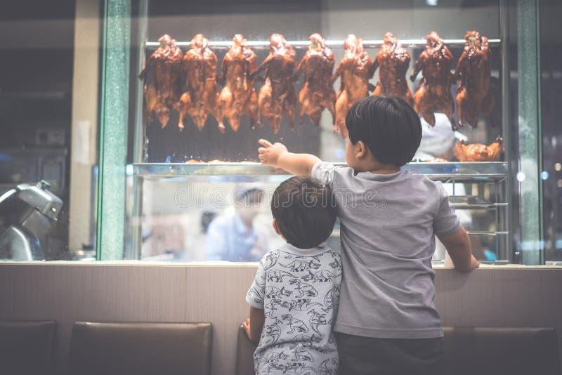 2个饥饿的兄弟观看一位厨师准备烤鸭子 免版税库存图片