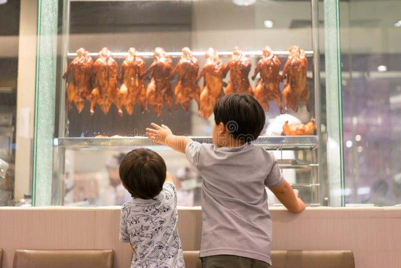 2个饥饿的兄弟观看一位厨师准备烤鸭子 免版税图库摄影