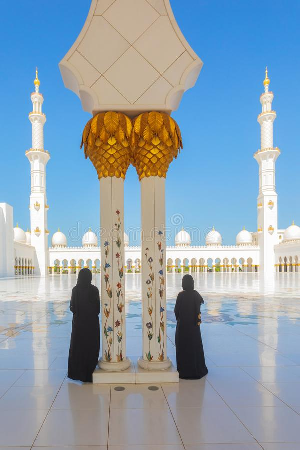 2个(;two);穿传统黑Abaya衣物的旅游妇女敬佩扎耶德Grand Mosque回教族长秀丽在Abu 图库摄影