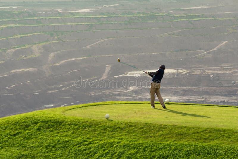 击中与俱乐部的高尔夫球运动员球在Beatuiful高尔夫球场 免版税库存照片