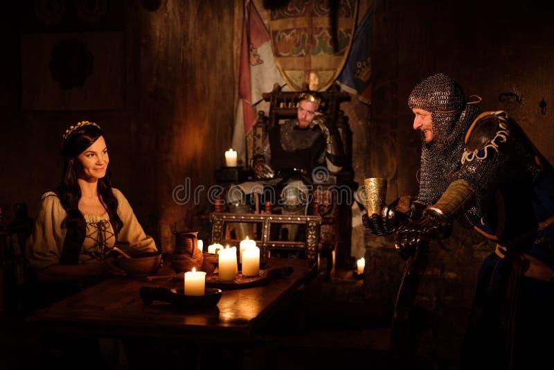 中世纪国王和他的主题在城堡的大厅里沟通 免版税库存照片