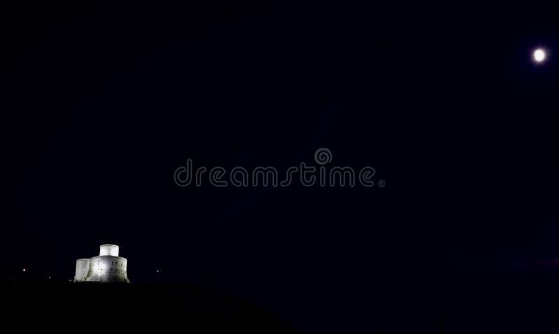 中世纪城堡和光亮的月亮的夜景 免版税库存照片