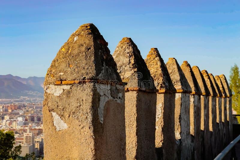 中世纪城堡的景色是历史悠久的Gibralfaro城堡城垛,位于西班牙马拉加市的山丘上 图库摄影
