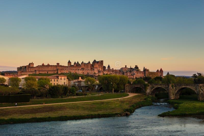 中世纪堡垒在距离的小山上升在河边区公园之上在卡尔卡松法国在日出 库存照片