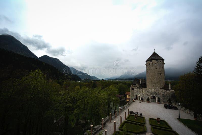 中世纪塔和庭院在奥地利山风景与阴云密布 库存图片