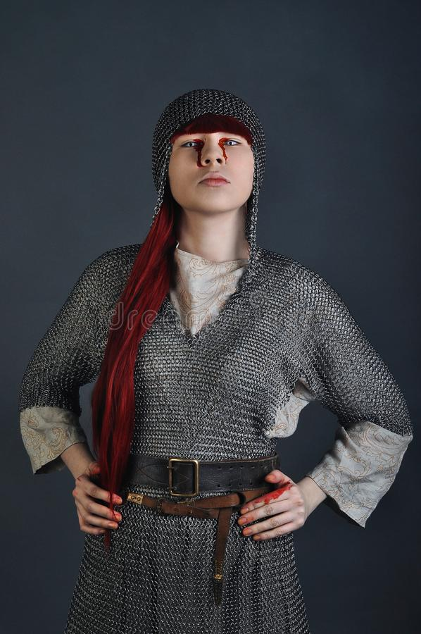中世纪女孩与红色头发的锁子甲在与血液的灰色背景站立在她的手上 免版税图库摄影