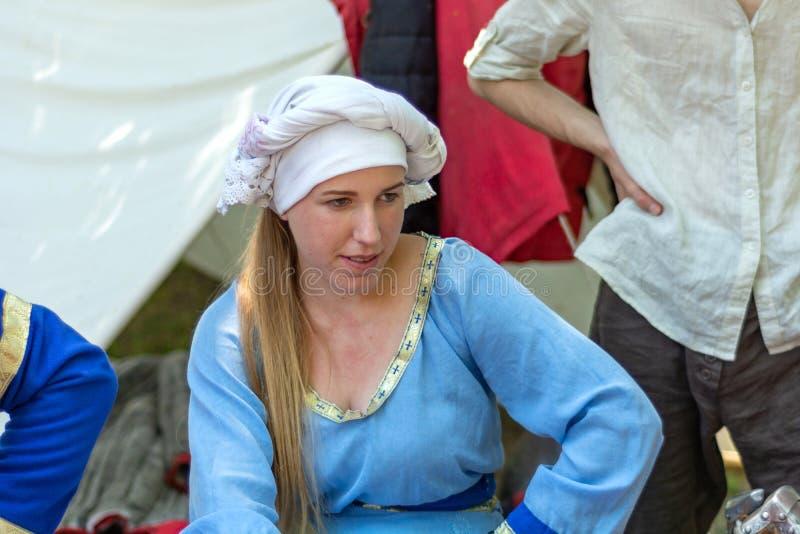 中世纪女孩的画象一件蓝色传统礼服和一个白色盖帽的 库存照片