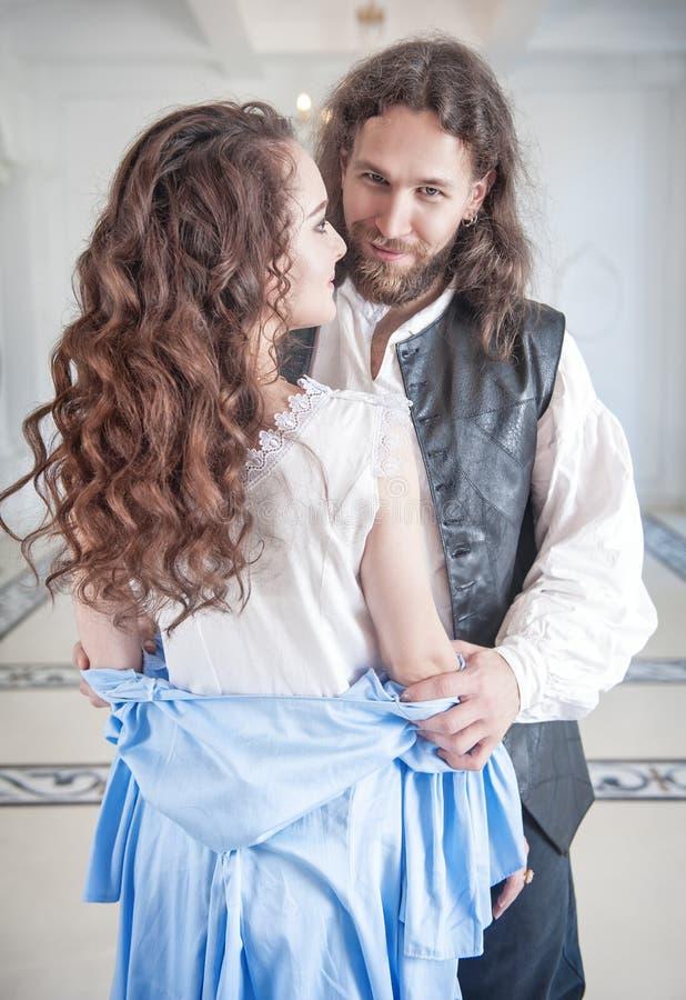 中世纪服装的英俊的人脱下衣服美丽的妇女 免版税库存图片