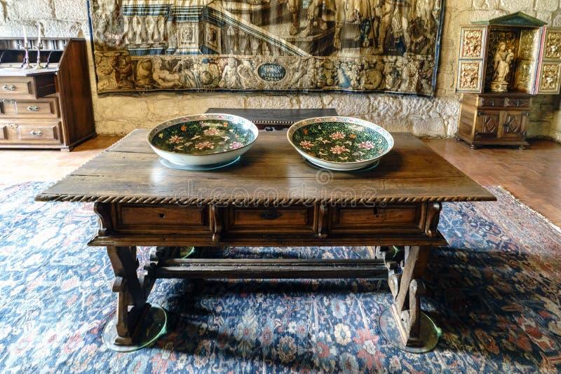中世纪木桌的细节与用花装饰的两个大喷泉的,在公爵的宫殿的中世纪设置 免版税库存图片