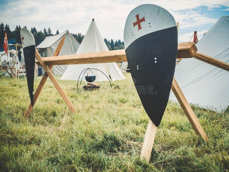 中世纪生活方式室外场面  有在篱芭固定家庭徽章的红色黑骑士盾 中世纪骑士attri 库存图片