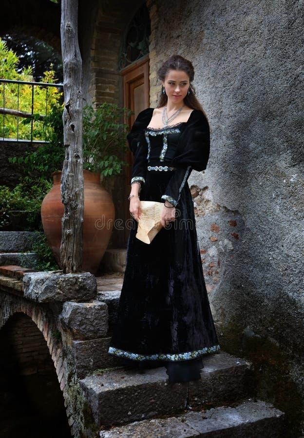 中世纪礼服的一美女有一封信件的在她的手上 图库摄影