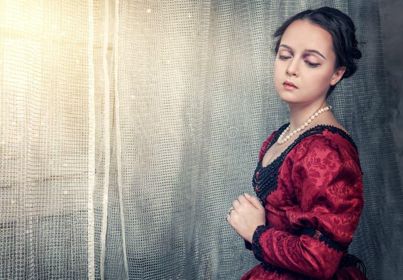 中世纪礼服的哀伤的美丽的妇女在窗口附近 库存照片