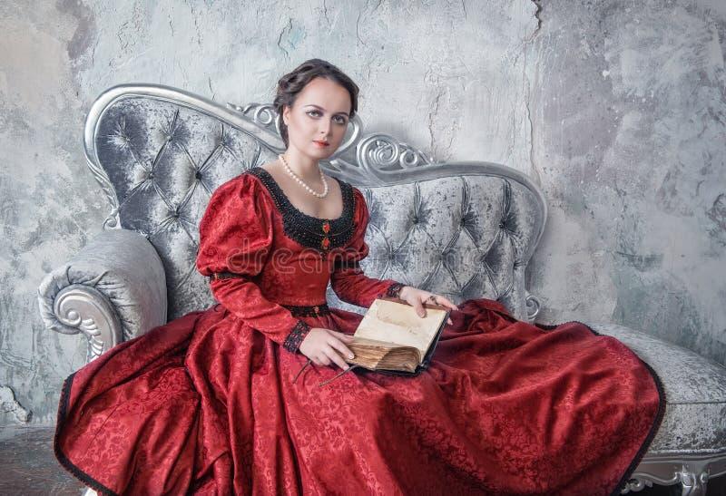 中世纪礼服的美丽的妇女在有书的沙发 免版税库存图片