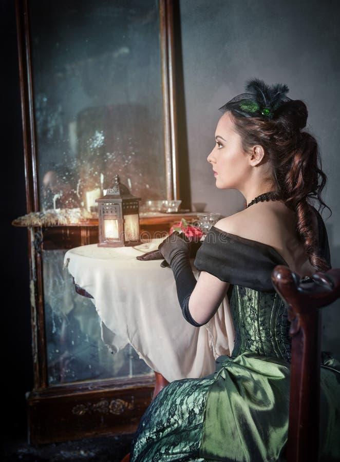 中世纪礼服的美丽的妇女在镜子附近 库存照片