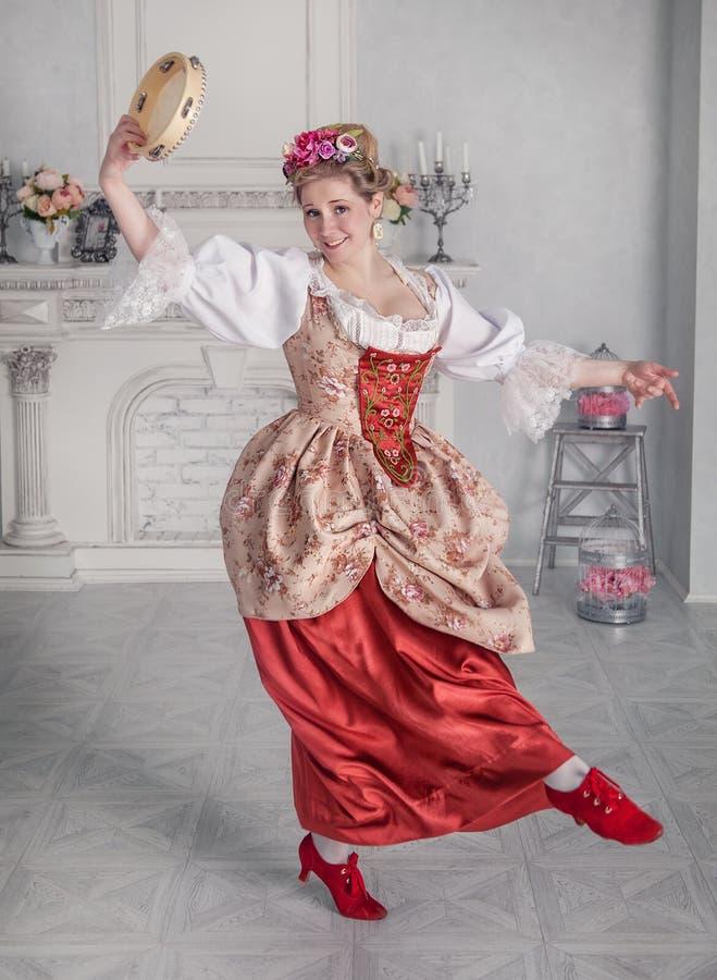 中世纪礼服的美丽的妇女有小手鼓跳舞的 免版税库存图片