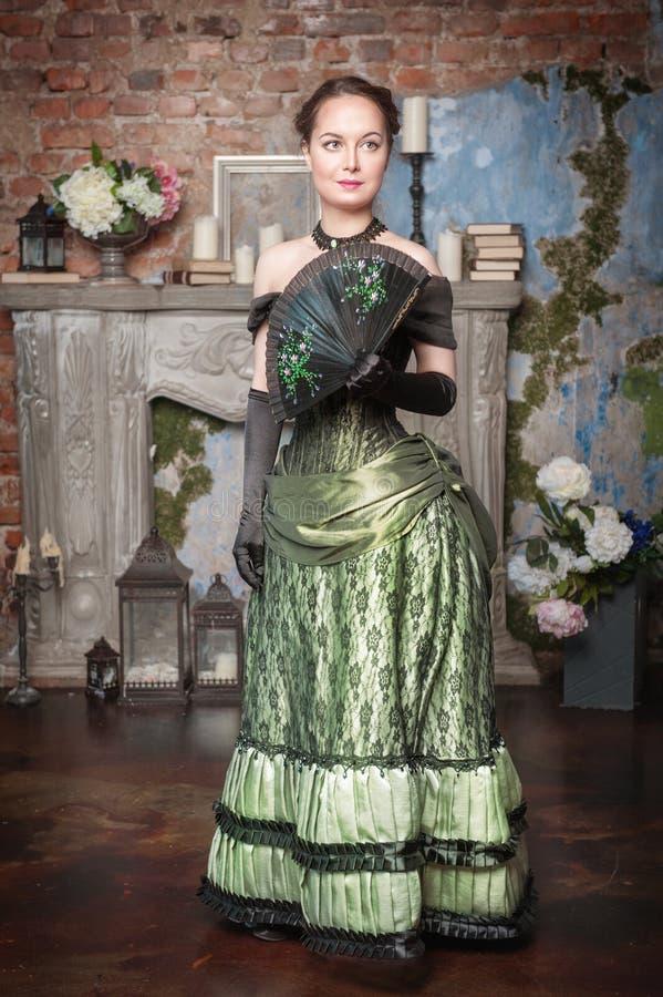 中世纪礼服的美丽的妇女有爱好者的 免版税库存照片