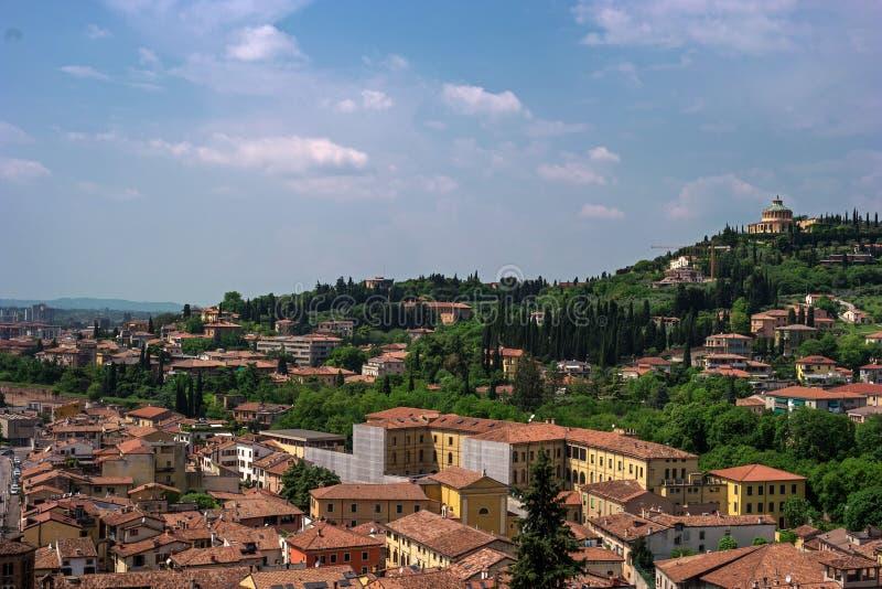 中世纪维罗纳,意大利的看法 铺磁砖的房子屋顶 在背景Santuario della玛丹娜二卢尔德 免版税库存照片