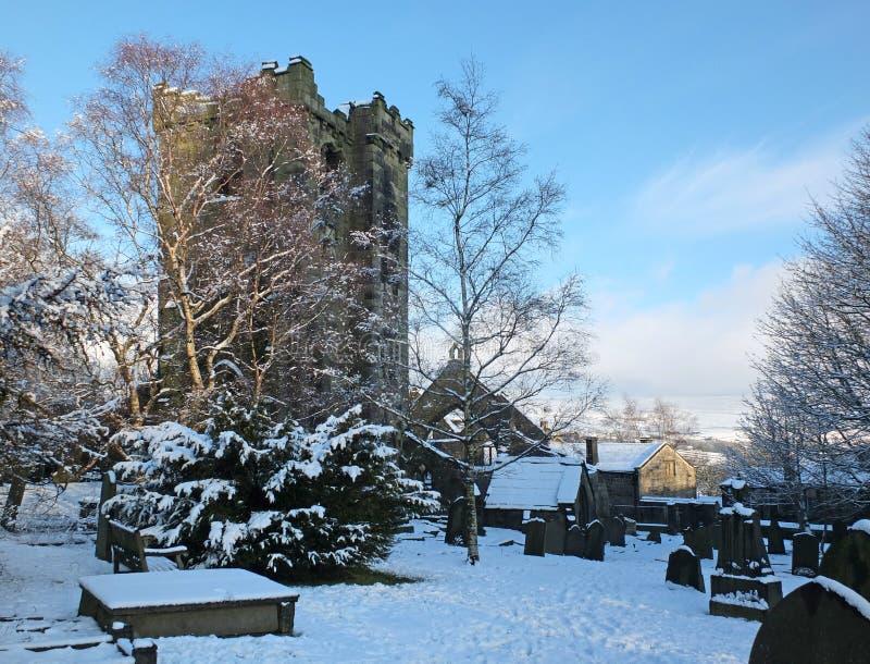 中世纪被破坏的教会的风景看法在雪包括的heptonstall西约克村庄用周围的坟墓 库存图片