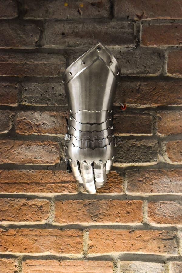 中世纪金属手套,一部分细节的古老装甲,战争细节  反对砖墙背景的发光的铁手套 免版税图库摄影