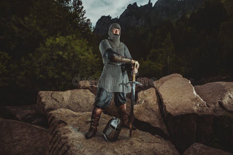 中世纪骑士在拿着剑的岩石站立 向量例证