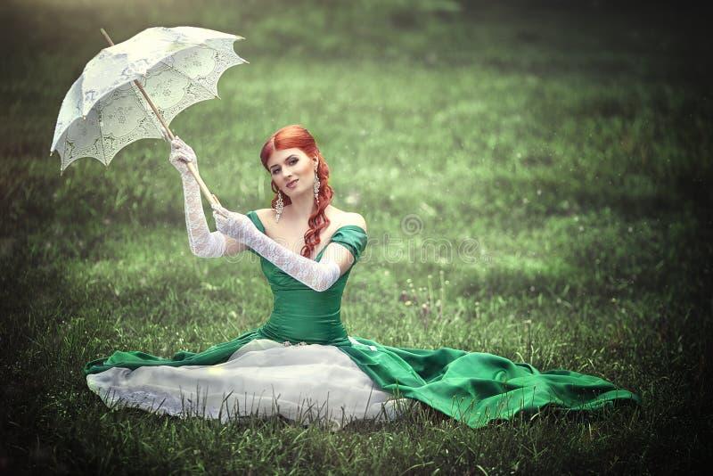 中世纪绿色礼服的美丽的年轻红发女孩有伞的坐草 免版税库存图片