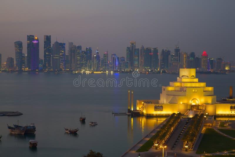 中东、卡塔尔、伊斯兰教的艺术多哈、博物馆&从东湾区的西湾中央财政区黄昏的 免版税图库摄影