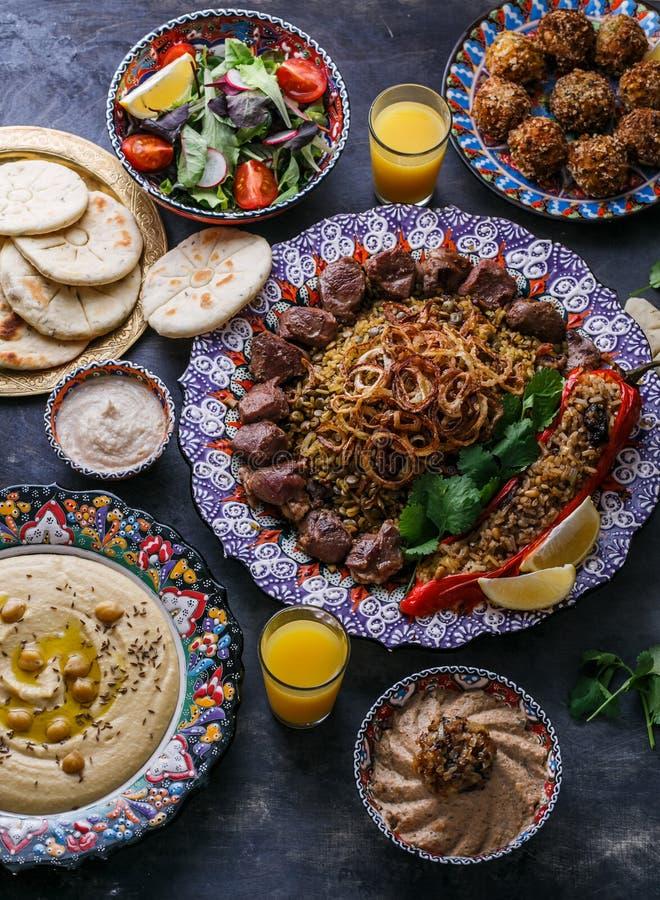 中东或阿拉伯盘和被分类的meze在黑暗的背景 肉kebab,沙拉三明治,酵母酒蛋糕ghanoush, hummus,米 免版税库存图片