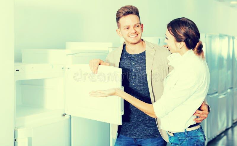 中产阶级选择新的冰箱的家庭夫妇 免版税库存照片