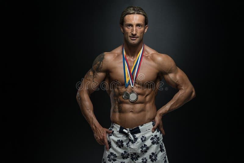 中古时期显示他赢取的奖牌的运动员竞争者 库存图片