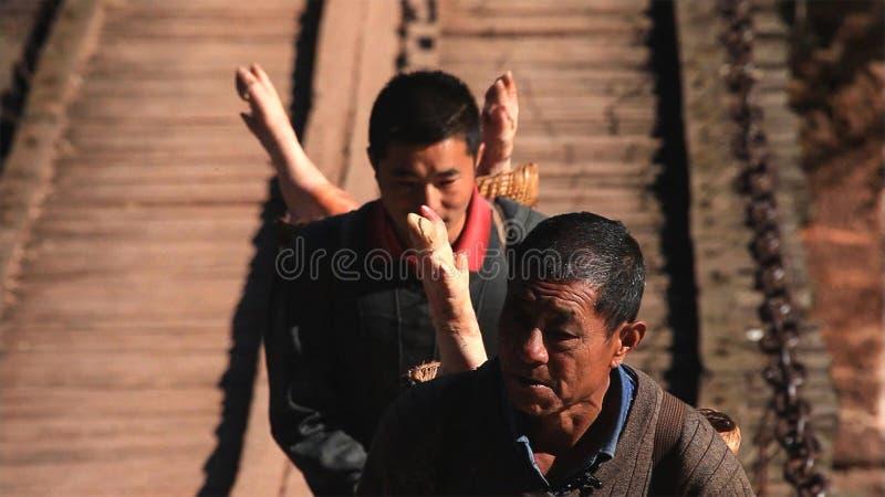 中国人在乡下市场上的运载猪 云南 中国 免版税库存照片