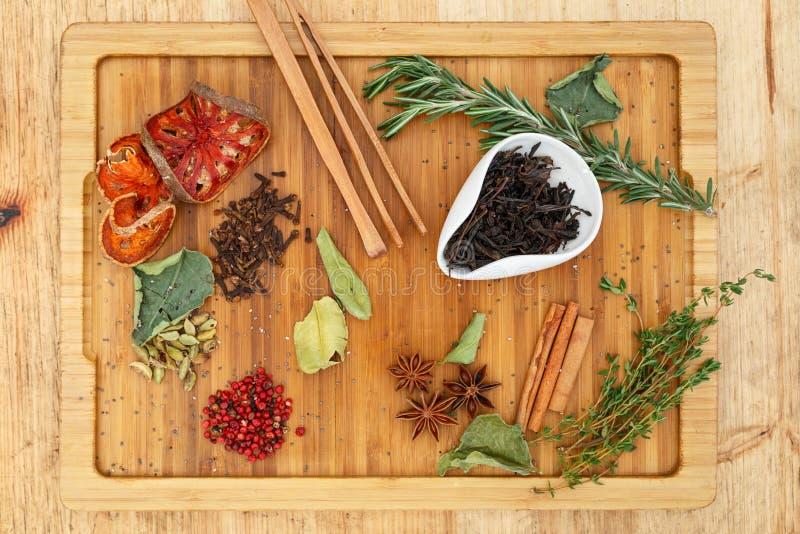 中国人Oolong红茶冯一个白色碗的黄旦康镇 在疏散茶的很多成份的一个木板上 免版税库存图片