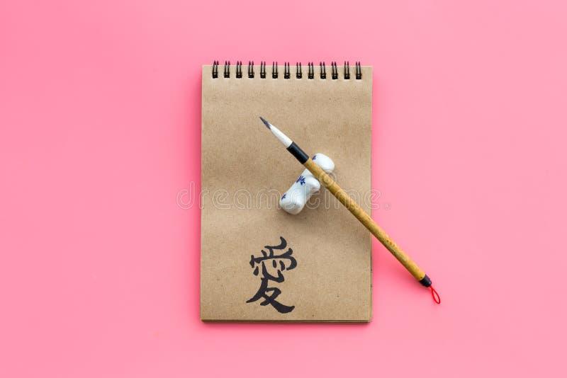 中国传统书法概念 在工艺纸笔记本的亚洲象形文字标志在特别书写笔附近  免版税库存图片