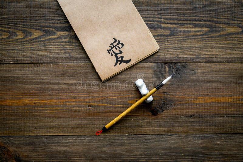 中国传统书法概念 在工艺纸笔记本的亚洲象形文字标志在特别书写笔附近  库存图片