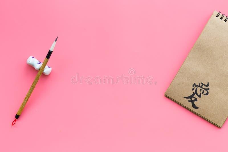 中国传统书法概念 在工艺纸笔记本的亚洲象形文字爱在桃红色的特别书写笔附近 免版税库存照片
