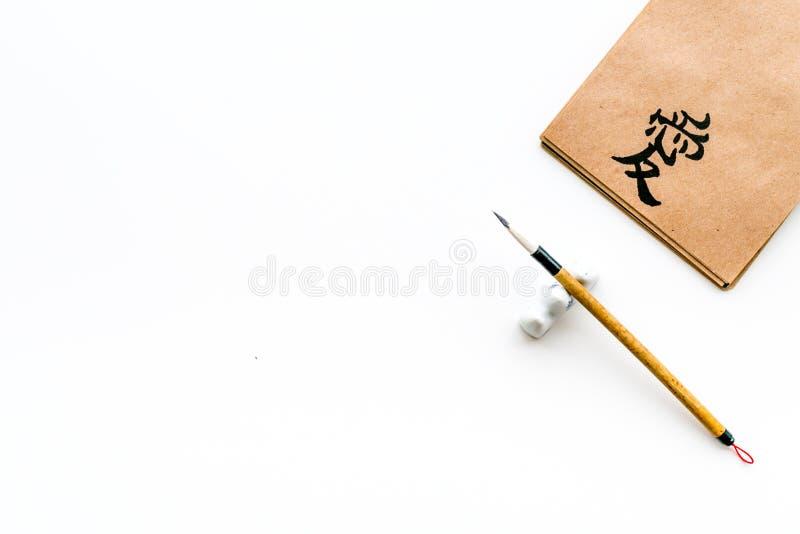 中国传统书法概念 在工艺纸笔记本的亚洲象形文字爱在特别书写笔附近  图库摄影