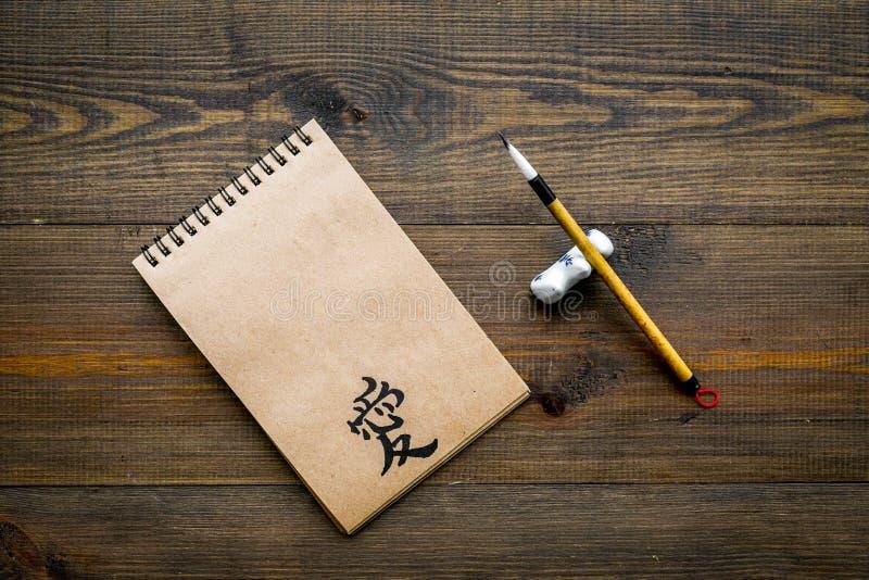 中国传统书法概念 在工艺纸笔记本的亚洲象形文字爱在黑暗的特别书写笔附近 免版税库存图片
